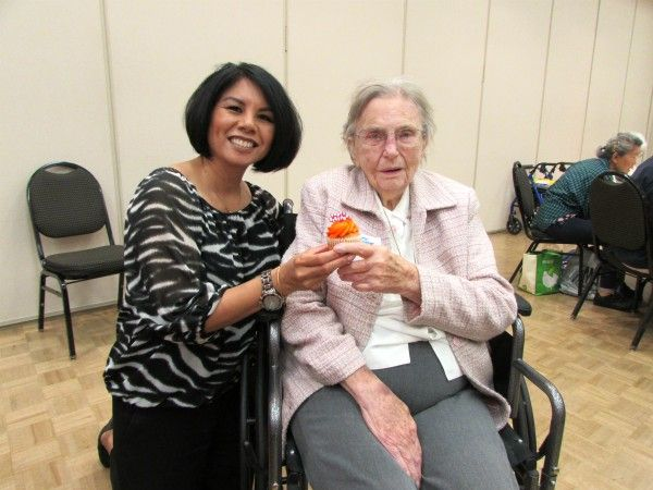 Grace Atwood with Senior with a Birthday cupcake at the Cypress Senior Center