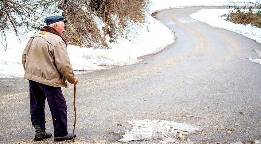 Elderly man with a cane walking down a snowy road.
