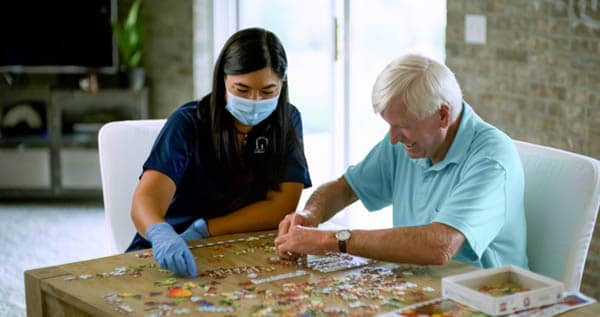 Female Right at Home caregiver helping a senior male put together a puzzle at a table in the home