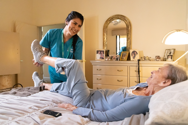 Female caregiver helping a senior female stretch her leg on a bed