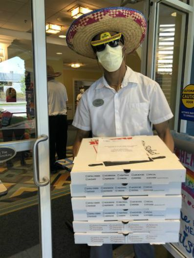 Man wearing a sombrero, while holding a stack of pizza boxes at the Bristal Assisted Living East Meadow, NY