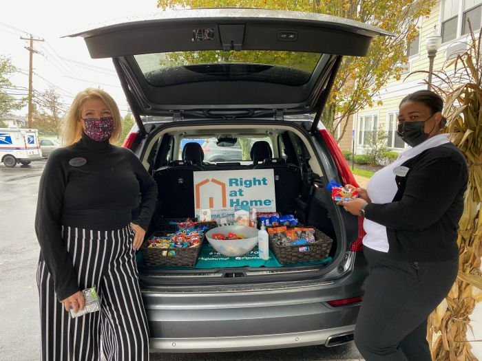 "Right at Home South Shore Long Island delivering refreshments to front line workers at the Bristal North Woodmere assisted living communities with a ""snackmobile"". Two females standing behind Right at Home vehicle with snacks in the back."