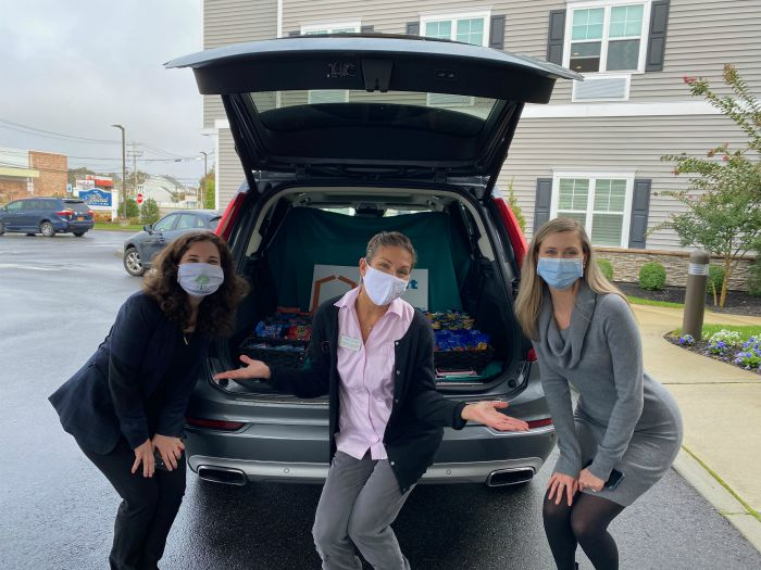 "Right at Home South Shore Long Island delivering refreshments to front line workers at the Bristal West Babylon assisted living communities with a ""snackmobile"". Three females standing behind Right at Home vehicle with snacks in the back."