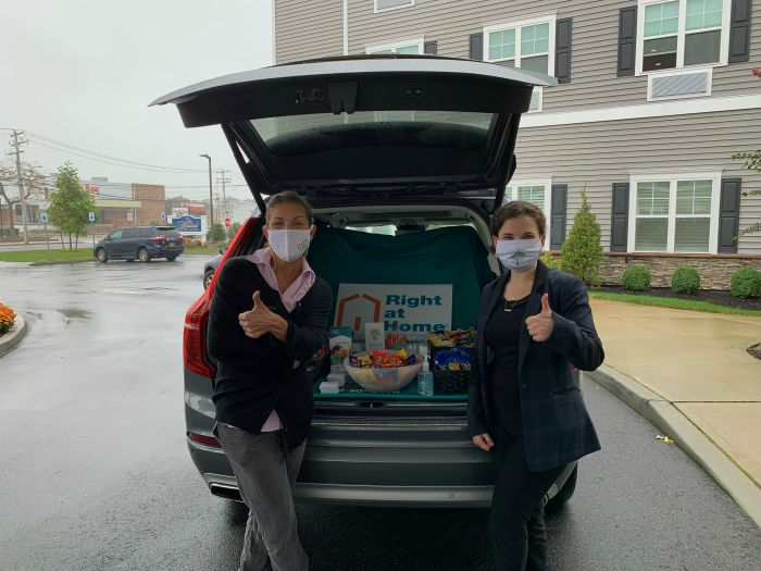 "Right at Home South Shore Long Island delivering refreshments to front line workers at the Bristal West Babylon assisted living communities with a ""snackmobile"". Two females standing behind Right at Home vehicle with snacks in the back."