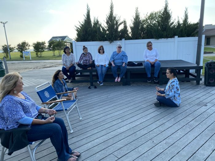 Eight people sitting outside, socially distant, for the NAIPC event to benefit the Alzheimer's Association and the Alzheimer's Disease Resource Center, at Tanner Park