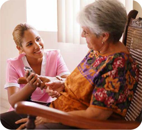 caregiver helping senior use remote control