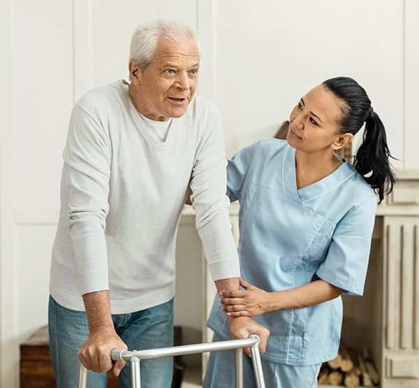 caregiver assisting senior to walk with walker