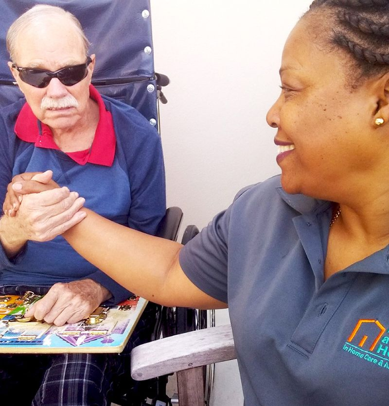 female caregiver caring for male senior client who is in a wheelchair