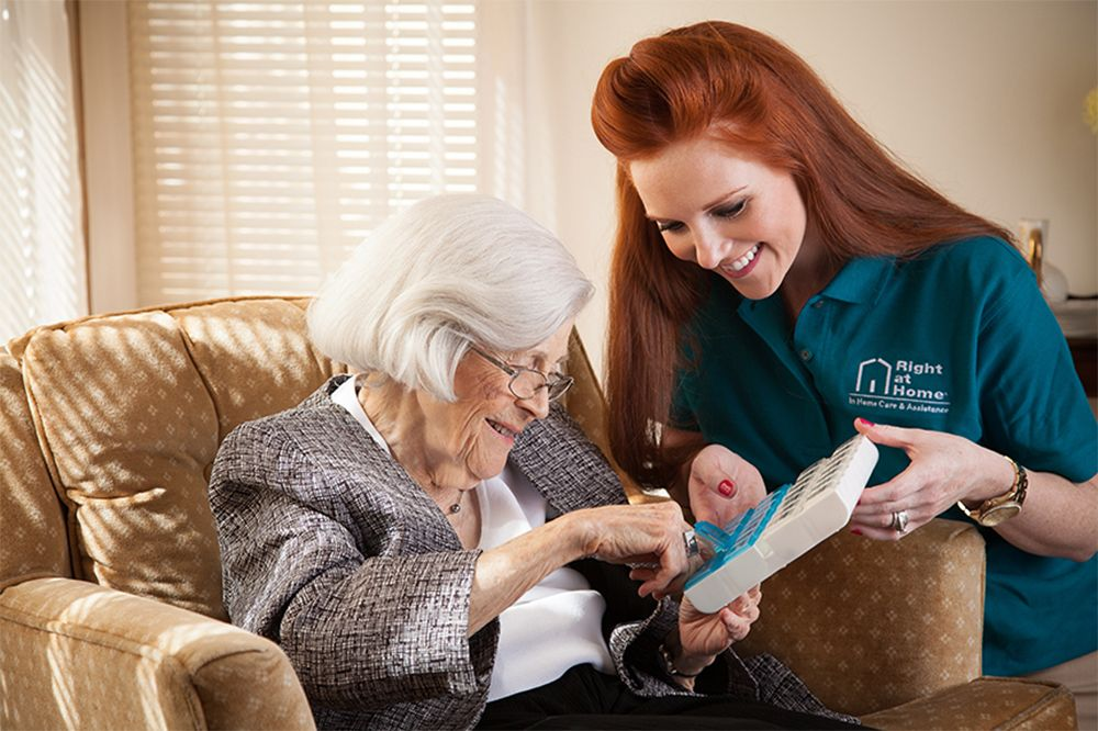 caregiver helping client by holding pill container and assisting on the right days