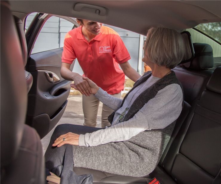 caregiver helping senior client out of car