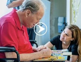 caregiver helping senior client in wheelchair celebrate a milestone