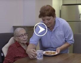 caregiver providing food for her senior client