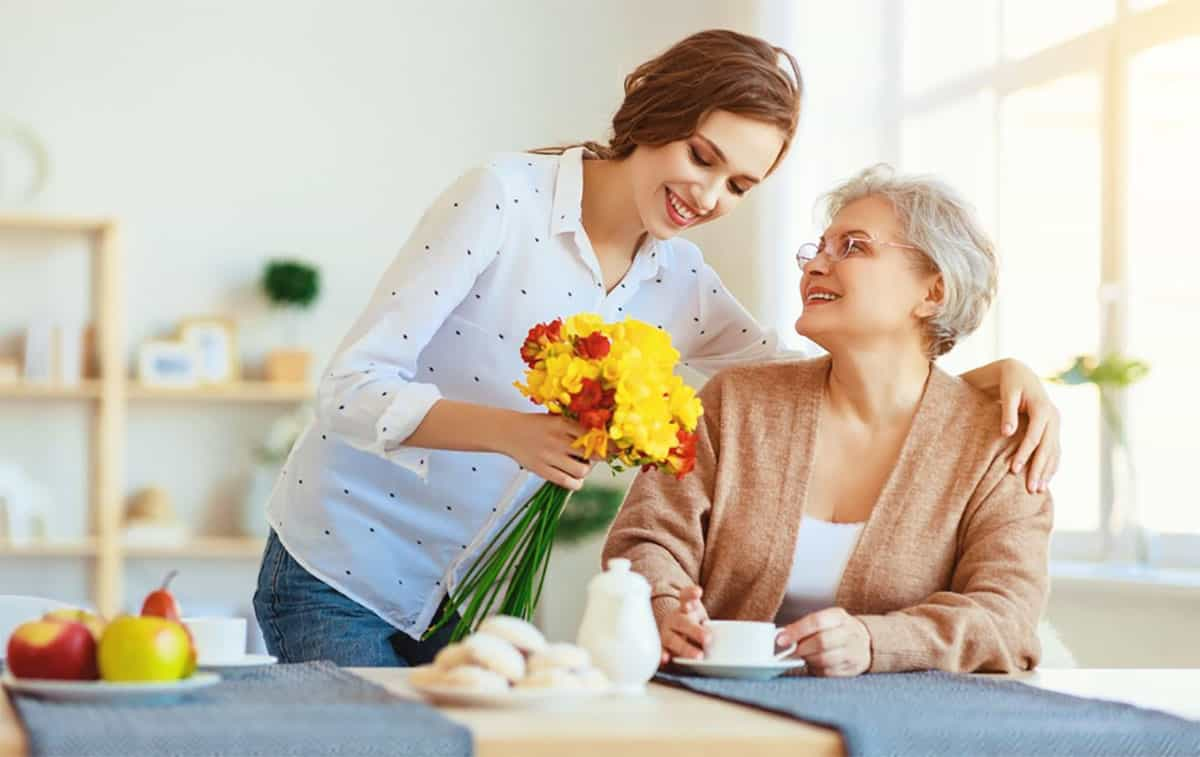 caregiver handing flowers to senior