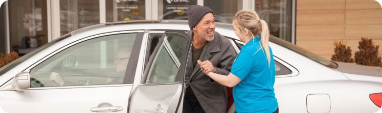 caregiver helping senior client out of the car