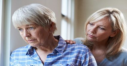 Senior Elderly Woman Looking Out Window While Woman Touches Her Shoulder
