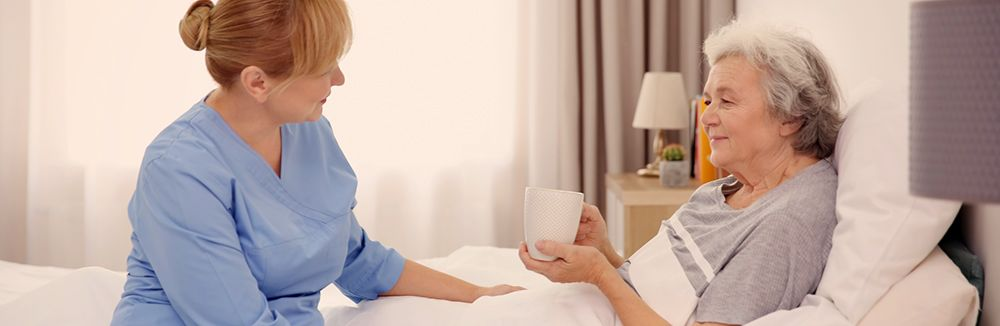 caregiver providing coffee for senior laying in bed