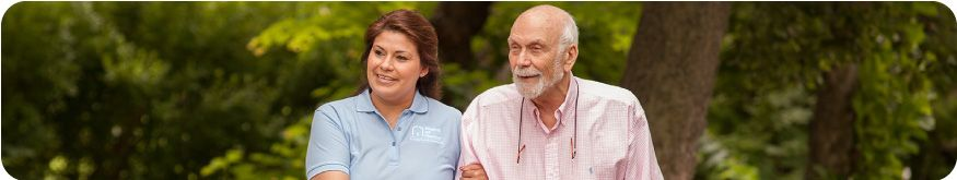 Female caregiver supporting a male senior client while walking