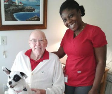 Right at Home Palm Beach Gardens caregiver smiling next to smiling senior client