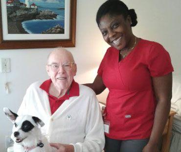 Right at Home Palm Beach Gardens caregiver smiling next to smiling senior client