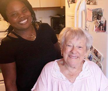 caregiver smiling next to smiling senior client