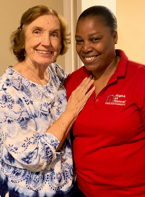Right at Home caregiver standing with a senior client