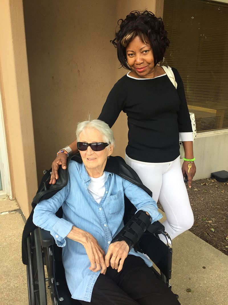 female caregiver standing next to senior client in wheelchair
