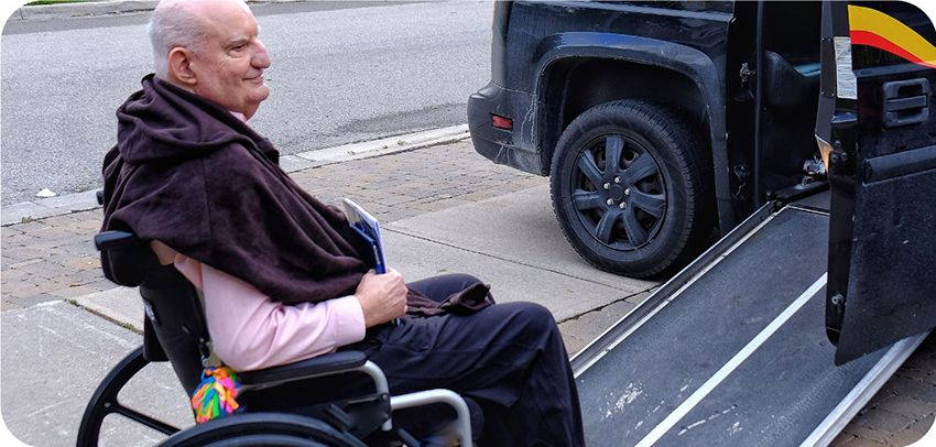 senior in wheelchair going up vehicle ramp
