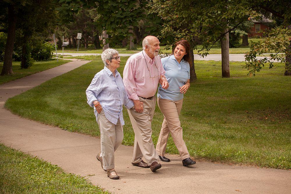 caregiver walking senior couple down the sidewalk