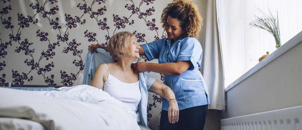 Caregiver assisting senior client to get dressed