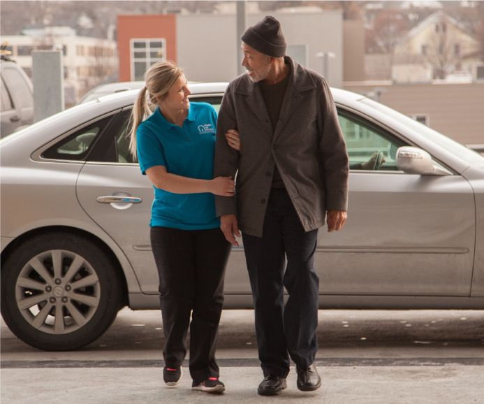 Caregiver helping senior client out of car and into appointment
