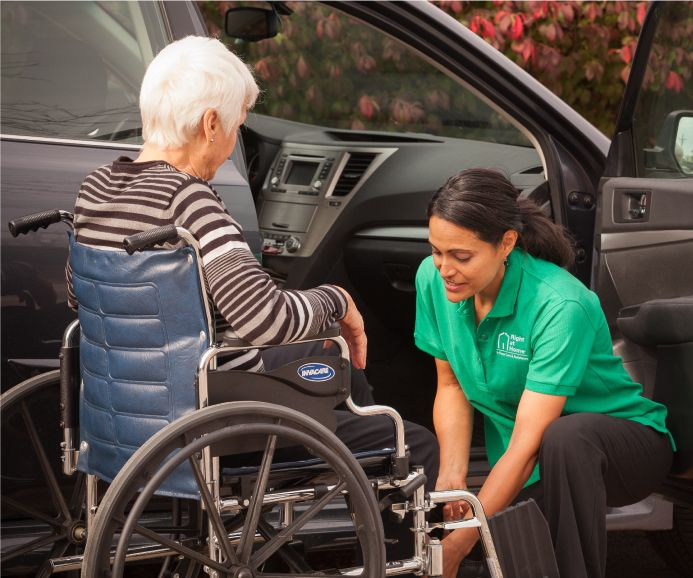 Caregiver helping senior client out of car and into wheelchair
