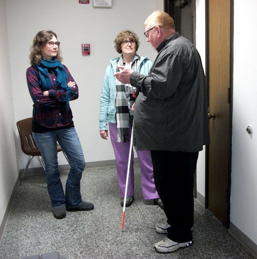 Three people standing in a hallway