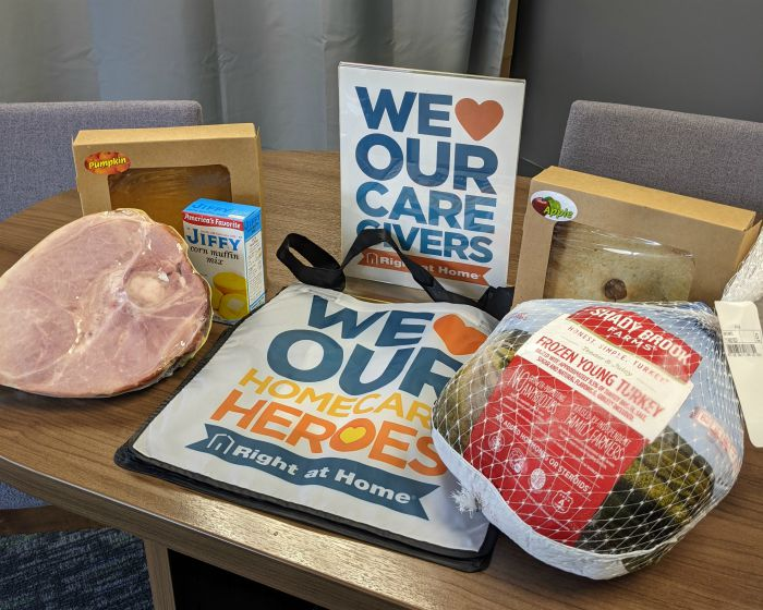 Thanksgiving turkey, ham, apple pie, and cornbread mix laid out for the caregiver appreciation bags, We love our homecare heroes at Right at Home Hudson Valley, NY