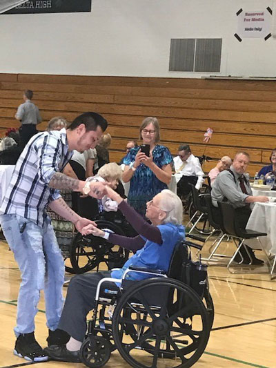 Man dancing with a senior woman in a wheelchair