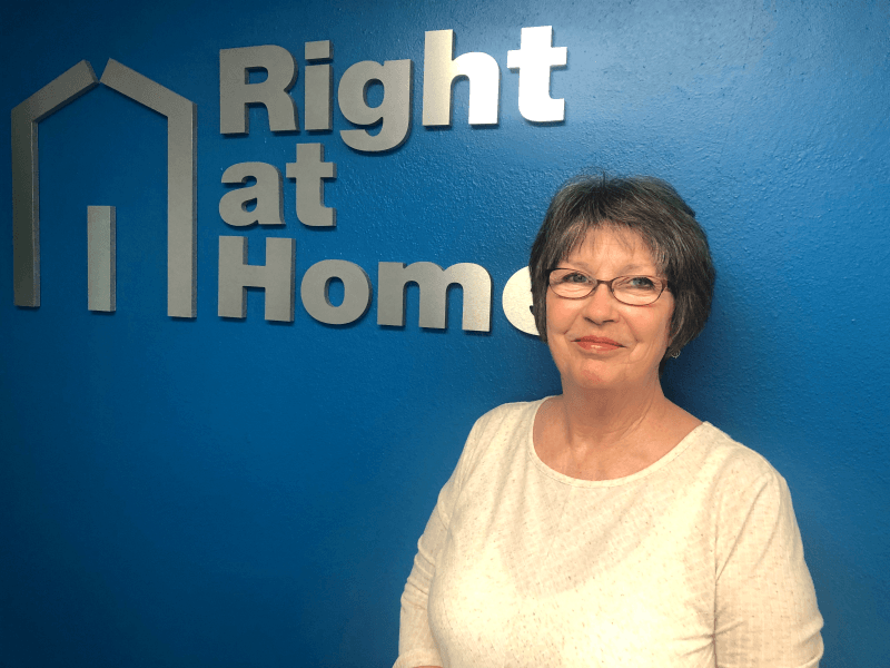 photo of Cindy King-Cordova, administrative assistant, against a blue wall with Right at Home sign