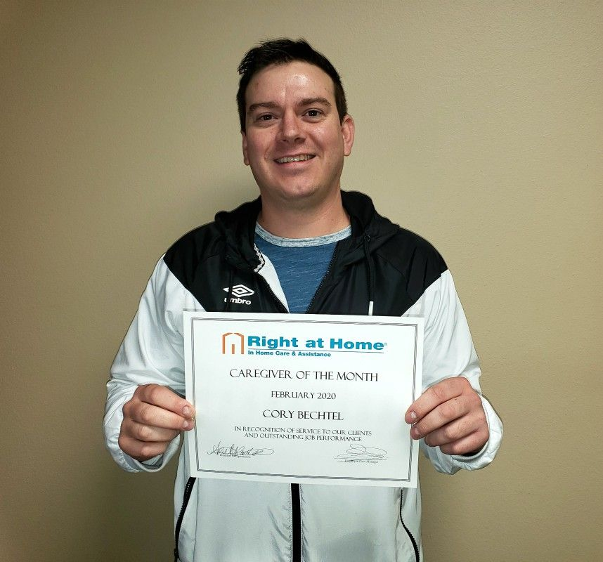 Cory B holding certificate for February Caregiver of the Month