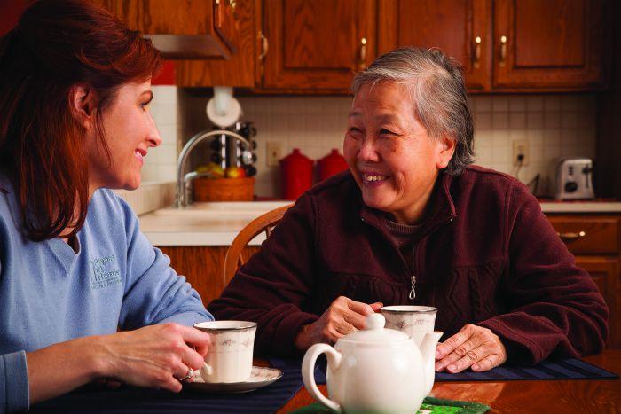 female caregiver enjoying coffee/tea with senior female