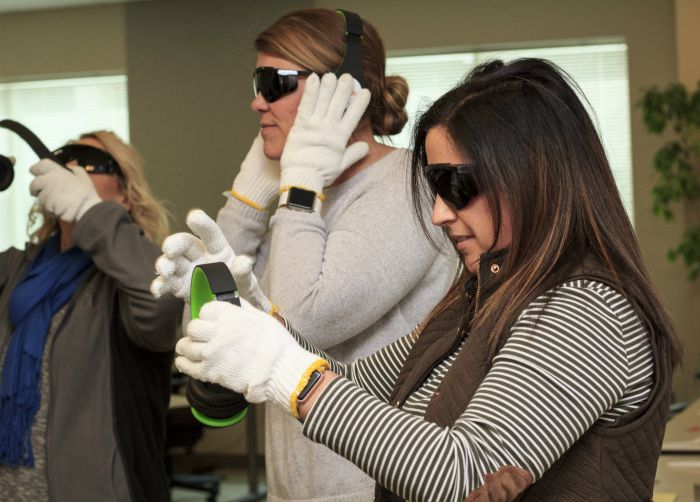 three females going through dementia live training with darkened glasses, thick gloves, special earmuffs.