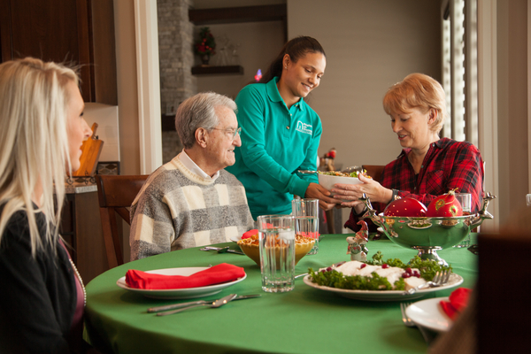 female caregiver helping serve a holiday meal to two seniors, one male, one female, and a younger female at a table in a dining room