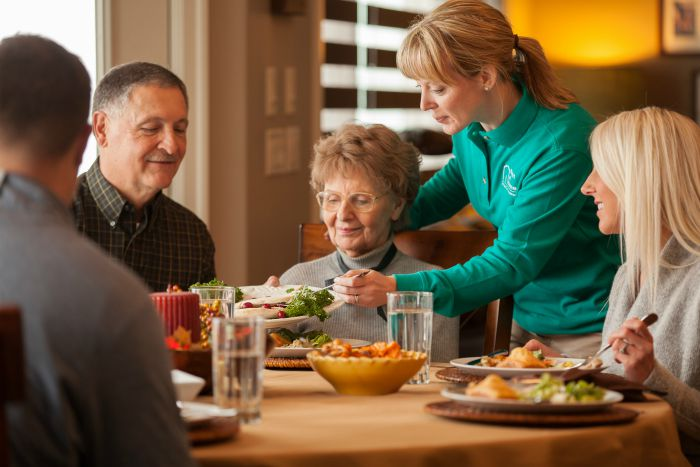 Female caregiver serving dinner to a family sitting at the table. The caregiver is serving food to a senior female member of the family's plate.