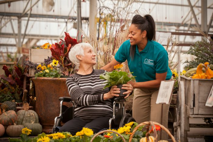 Senior female in wheelchair with female caregiver shopping for flowers