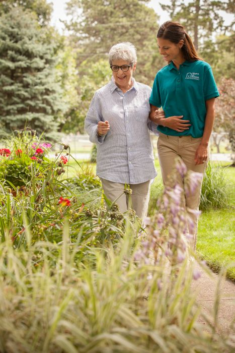 Female caregiver escorting a female senior on a path next to flowers, outside