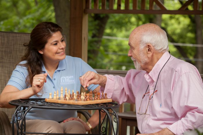 Female caregiver playing chess with a senior male