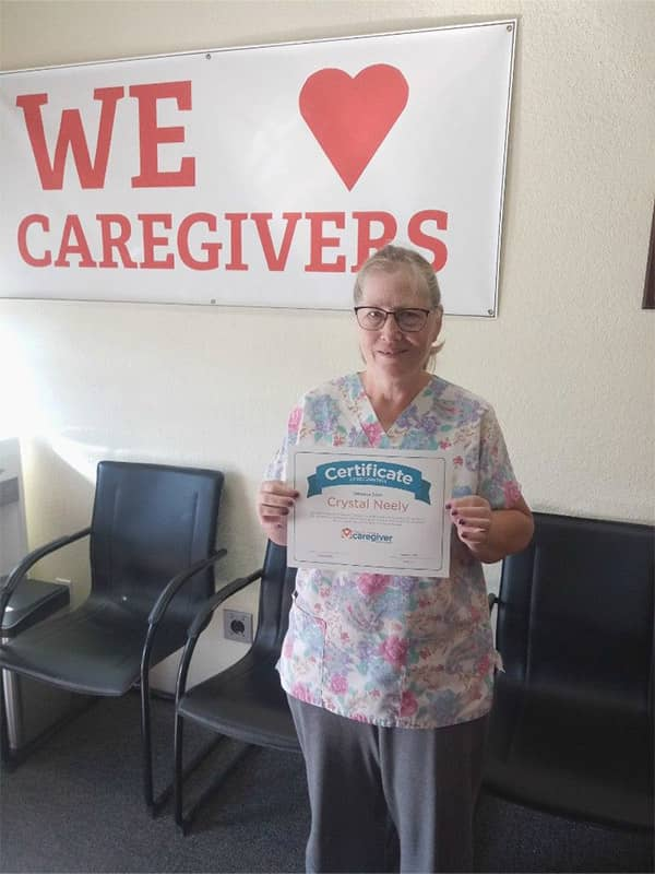 Crystal standing in front of the We Love Our Caregivers sign with her certificate for Employee of the Month