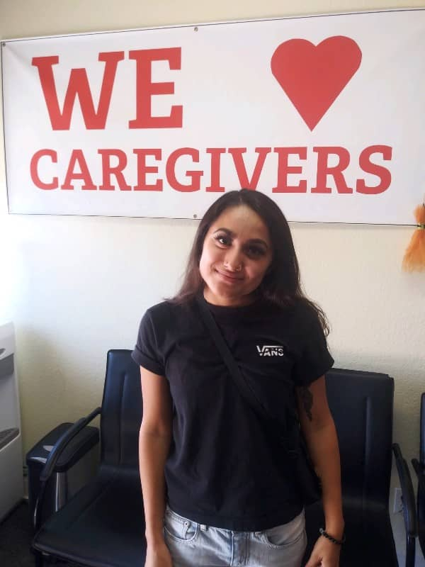 photo of Katarina standing in front of We heart Caregivers sign