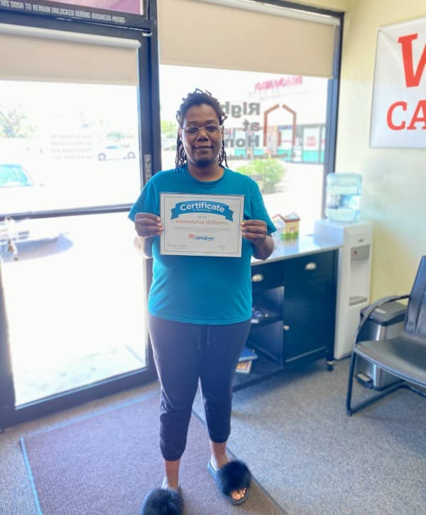 Kimmeshia standing holding employee of the month certificate