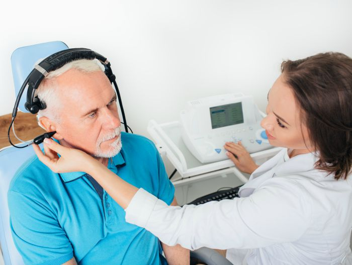 Senior male receiving a hearing test from a female doctor of audiology