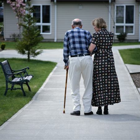 Senior man walking with caregiver.