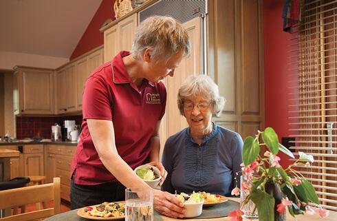 Caregiver serving senior lunch