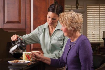 caregiver pouring coffee for senior client